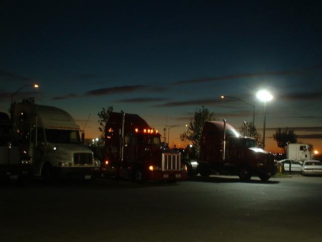 nákladní automobily v řadě, tři stojí v řadě vedle sebe, je tma, svítí pouliční lampa